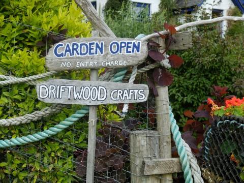 Driftwood signs proclaim 'Garden Open'.
