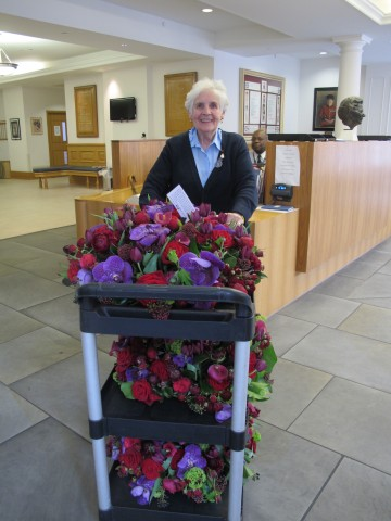 A trolley brimming with richly hued bouquets waiting to be distributed.