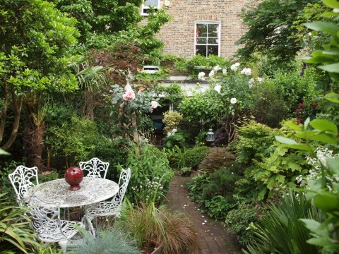 62 Hungerford Road, London N.7.  A densely planted mature garden with several different seating areas.
